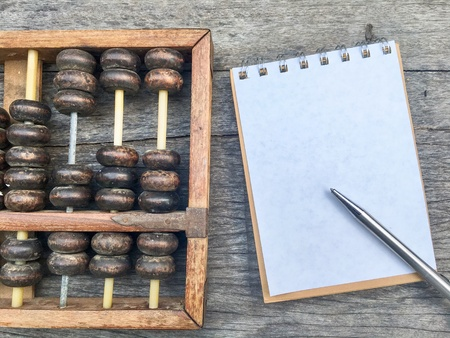 Abacus on wooden background beside notebook and pen.