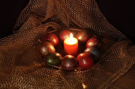 paschal egg in the nest of easter rabbit with candle photo