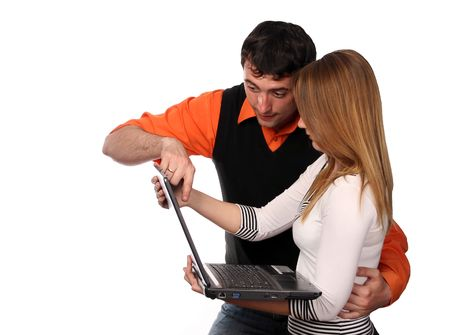 couple working with laptop, pretty blonde and handsome young dark haired man Stock Photo