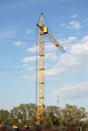 yellow lifting crane over blue sky with clouds photo