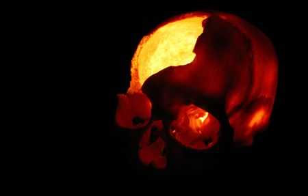 Burning skull - Old broken skull against black background with inner flame photo