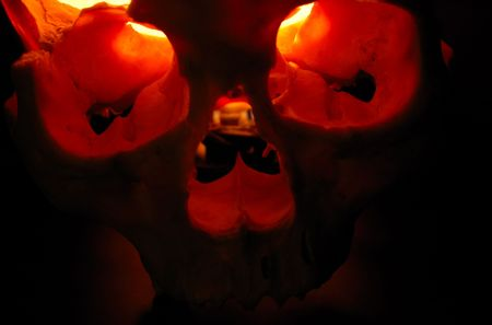 Front of burning skull - old skull against black background with inner flame photo