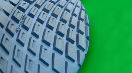 nonslip: macro pattern of rubber sole of sneakers against green
