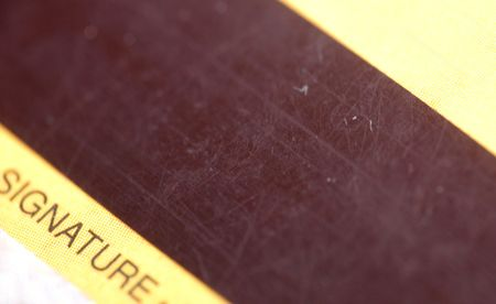 macro pattern of pretty used magnetic strip of credit card, contain word  photo