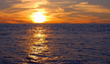 oceans sunset with gold sunbeam over water photo
