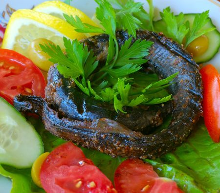 asian food - fried stone eel (lamprey, snake-like fish) and vegetables photo