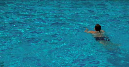 swimming boy and pattern of water of swimming pool with light in it photo
