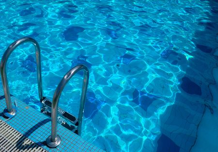 pattern of water of swimming pool with light in it and pools stairway photo