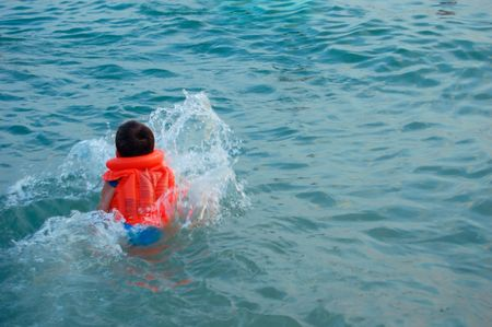 swimming boy with life jacket and pattern of water of sea photo