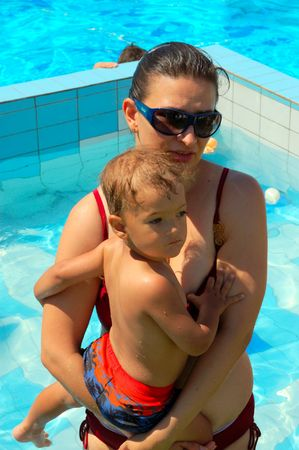 mother and little son at swimming pool having fun photo