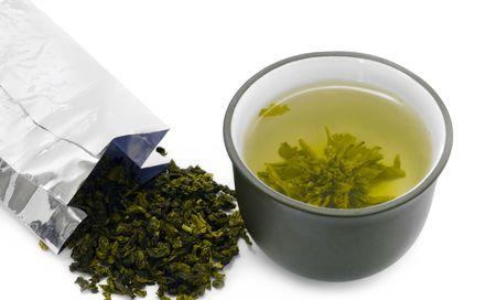 hojas de te: taza de t� y el paquete de hojas de t� verde  Foto de archivo