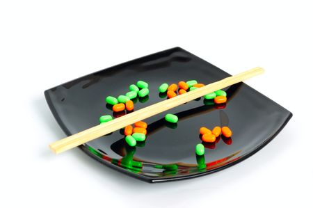 chemical diet - colored pills on black asian plate and chopsticks photo