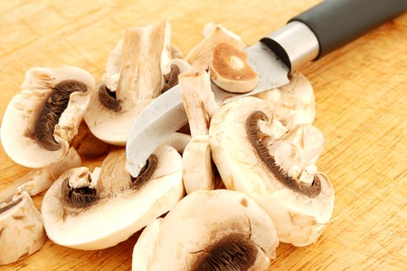 bended: cutted raw champignons and bended knife