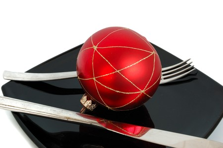 holyday: holyday diet concept - black plate and xmas decoration - shiny red ball