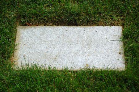 möglicherweise: Stein-Platte in Gras (vielleicht Grabstein) mit copyspace