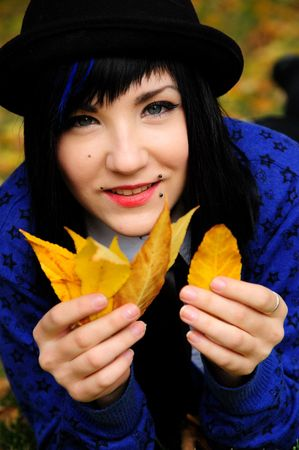 funny young pretty long haired blue-eyed  brunette  playing with autumn leaves photo