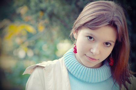 funny young pretty long haired hazel-eyed  brunette in autumn leaves (crossprocwssed) photo