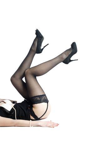 piernas con tacones: piernas de la ni�a en stokings negro sobre blanco Foto de archivo