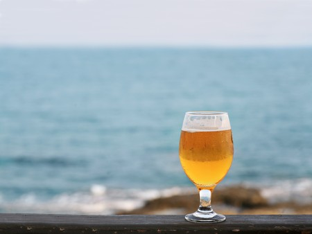 one glass of beer against sea and coastline