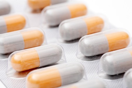 blister pack of white-orange pills isolated on white background photo