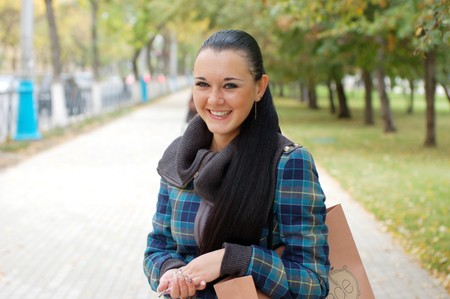young pretty black haired girl outdoors in autumn street photo