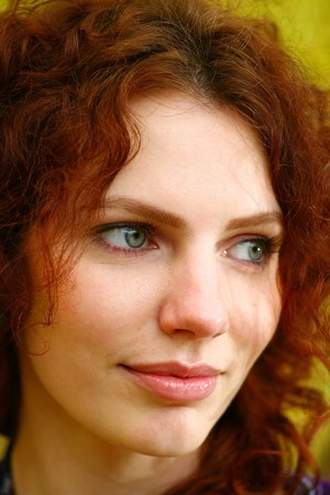 face in tree bark: Portrait of a redheaded girl near a tree (autumn colors). Stock Photo