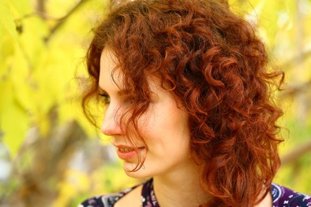 Portrait of a redheaded girl near a tree (autumn colors). Imagens