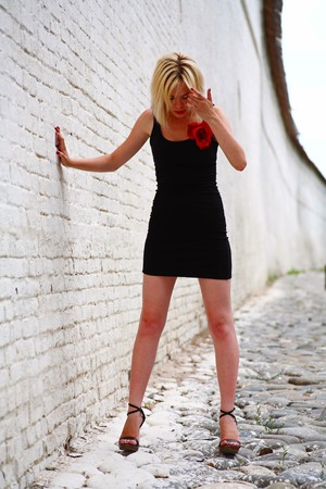 Blonde female fashion model in sexy dress against a brick wall background Stock Photo - 8092693