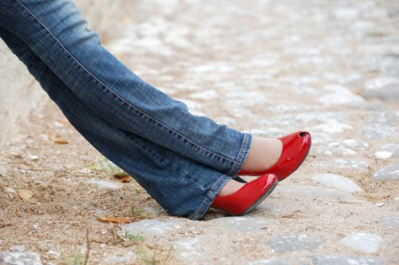 legs in jeans and red shoes photo