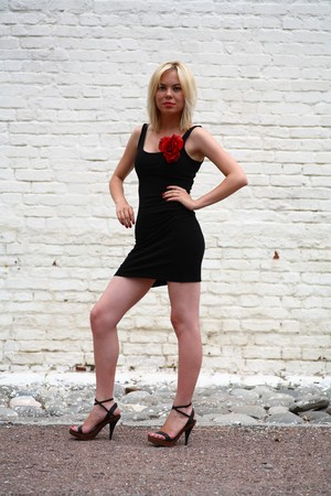 beautiful young girl in black dress with red flower against a brick wall photo