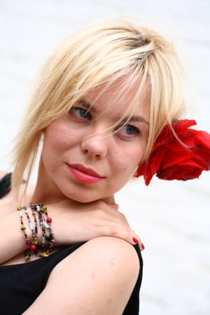 A stunningly beautiful young blond woman with red flower in hair Stock Photo - 8111232