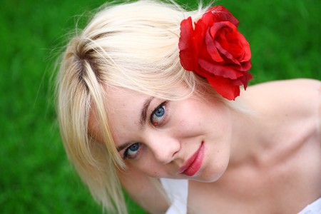 A stunningly beautiful young blond woman with red flower in hair photo