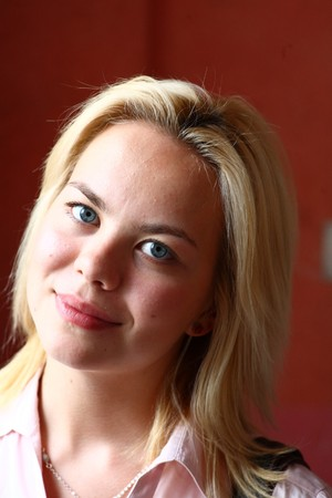 A stunningly beautiful young blond woman with bright blue eyes against wall photo