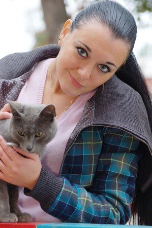 young pretty black haired girl outdoors in autumn on playground with cat photo