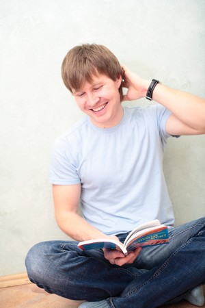 relaxed man sitting on the floor with book photo
