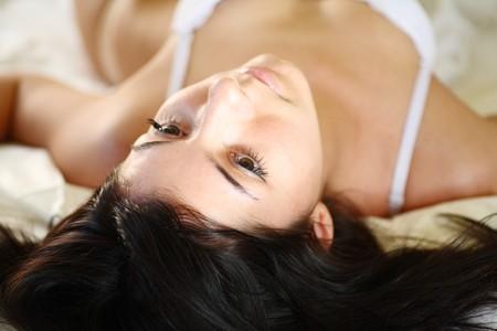 european fashion model posing in bed wearing white underwear photo