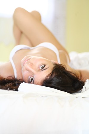 european fashion model posing in bed wearing white underwear photo