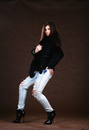 attracive: attracive young woman in a fur coat and jeans on brown background