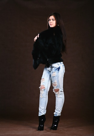 attracive young woman in a fur coat and jeans on brown background photo