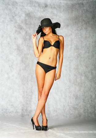 sexy brunette in black bikini and bonnet isolated on white background Stock Photo - 9283542