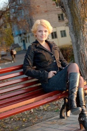 Beautiful girl on a park bench alone photo