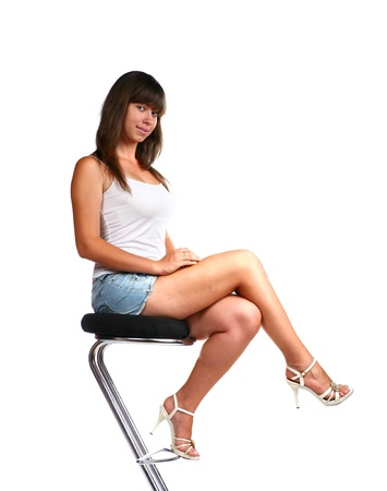 high heels woman: beautiful blond female wearing jean shorts and top on white sitting