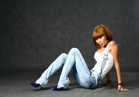 Beautiful Japanese girl in jeans over dark grey background photo