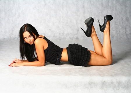 tempting concept - sexy well tanned brunette on the gray background undressing Stock Photo - 9373426