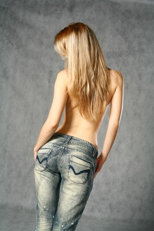 bare women: beautiful young blond woman in jeans ( back side) studio shot
