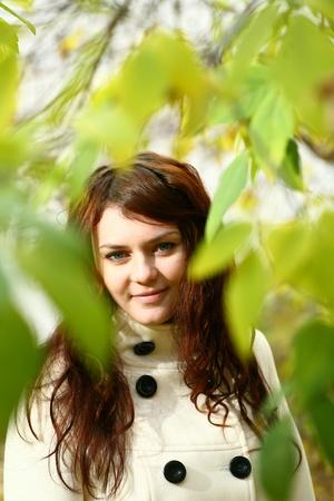 Portrait of a redheaded girl near a tree photo