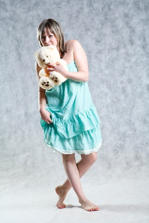 A beautiful and sexy 20-25 years blond girl with teddy bear  in dress on grey background photo