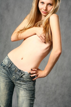 bare chest: beautiful young blond woman in jeans studio shot