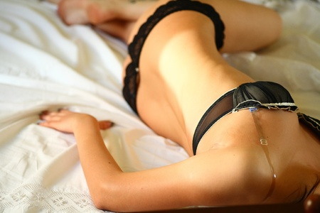 european fashion model posing in bed wearing black underwear