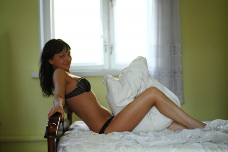 bra top: european fashion model posing in bed wearing black underwear